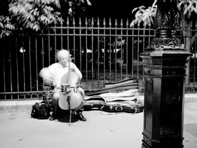 French cellist in mid-performance on a sidewalk
